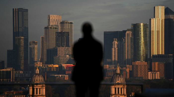 The morning sunlight illuminates the office buildings of the Canary Wharf financial district