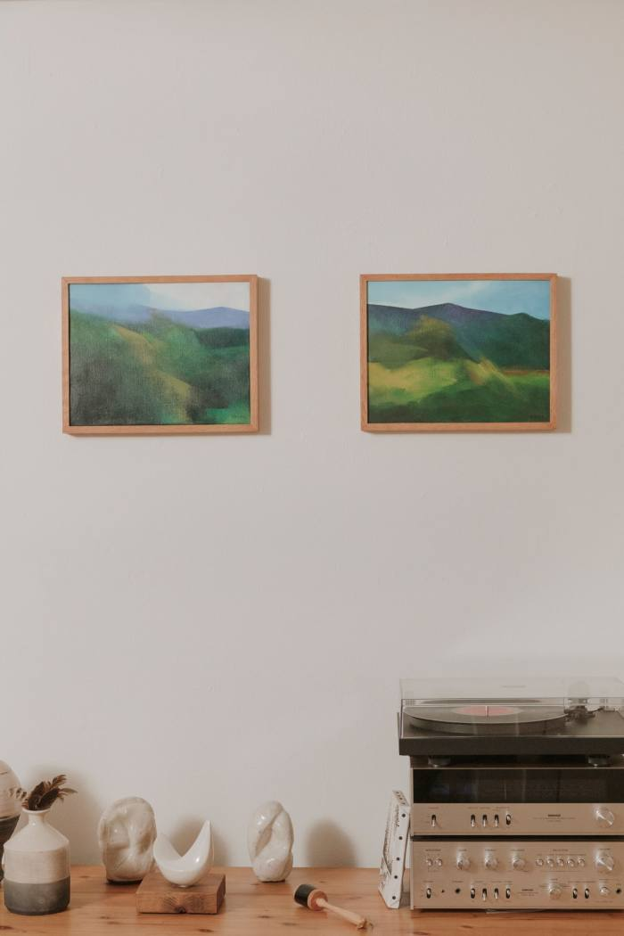 The two abstract paintings of Jamaica's Blue Mountains by George Rodney that Johnson has owned since childhood, above pottery made by her father