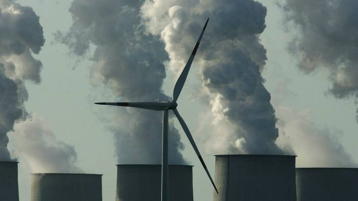 A loan wind turbine spins as exhaust plumes from cooling towers at the Jaenschwalde lignite coal-fired power station