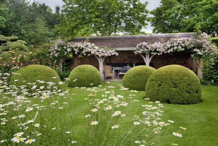 Balls of box hedge by the loggia at Wollerton Old Hall in Shropshire