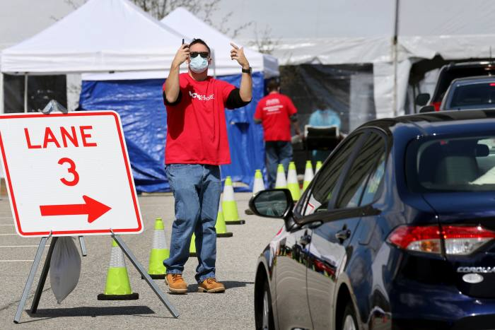 LOWELL, MA - APRIL 7: A man directs vehicles as they arrive at a rapid COVID-19 testing site in Lowell, MA on April 07, 2020.