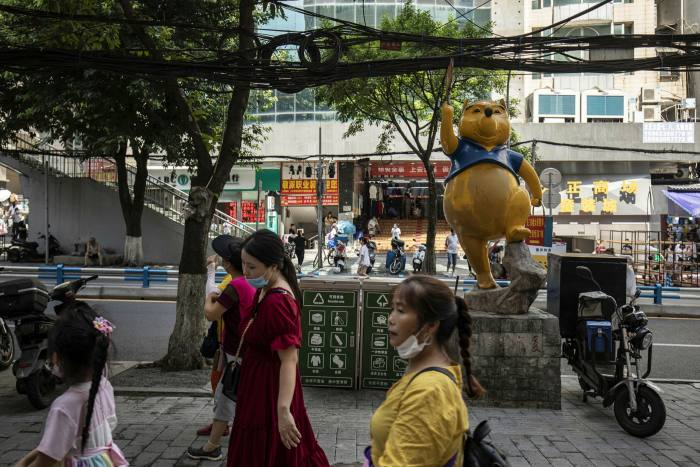 Pedestrians pass a stall in Chongqing.{ er capita consumer spending by urban residents — mainly low to middle income groups — fell 6.2 per cent in the second quarter of 2020