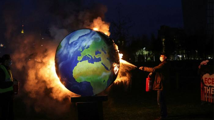 An environmental activist extinguishes a burning a model of the Earth during a climate protest