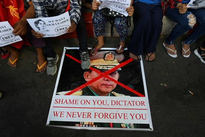 Protesters step on a banner showing an image of Myanmar military chief Min Aung Hlaing during a demonstration in Yangon