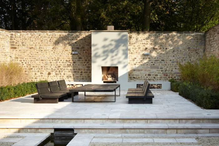An outdoor living space with a fireplace that was recently created by Fiona Barratt-Campbell