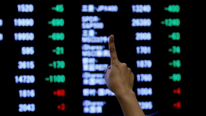 A woman points to an electronic board showing stock prices