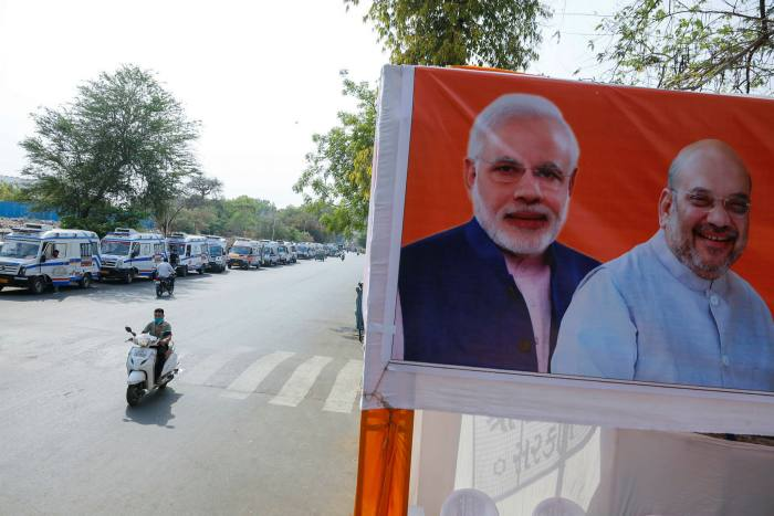 A long line of ambulances carrying Covid patients waits outside a hospital, within sight of portraits of Narendra Modi and his deputy Amit Shah