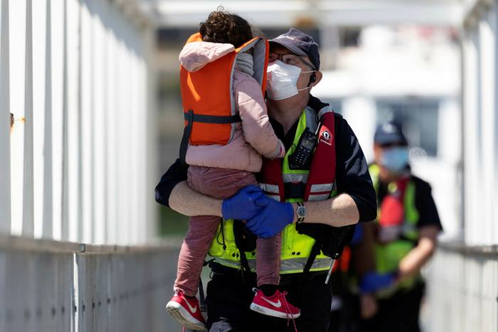 A UK Border Force official holds a young girl who arrived with other migrants after being picked up in a dinghy in the English Channel this summer