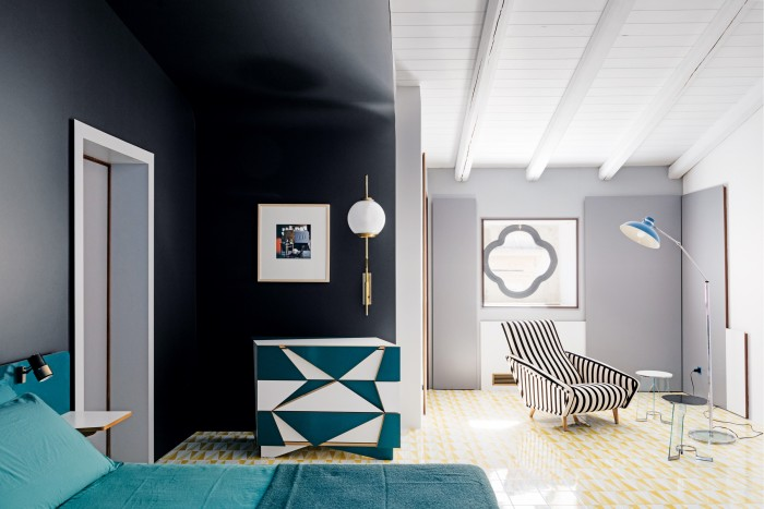 A bedroom with aGamper cabinet, a1962 Ugo Mulas print (on the darker wall) and a 1950 chair and 1930s tables by Ponti