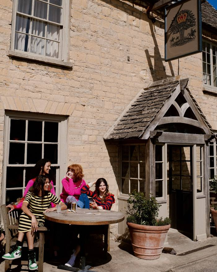 From left: Scarlett wears Bella Freud cotton cashmere dress, £225. Nike vintage trainers and socks, both Scarlett's own. Megan wears Philosophy cashmere jumper, £435. Edwina wears Philosophy wool jumper, £910. Primrose wears Philosophy cashmere jumper, £365. Erdem denim jeans, £420. Converse cotton sneakers, £57. Socks, Primrose's own.