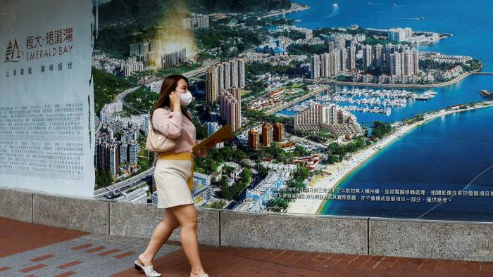 A woman walks past a property advertisement for Emerald Bay by China Evergrande in Hong Kong
