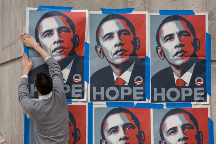 A supporter pastes up posters of Barack Obama in Austin, Texas, 2008