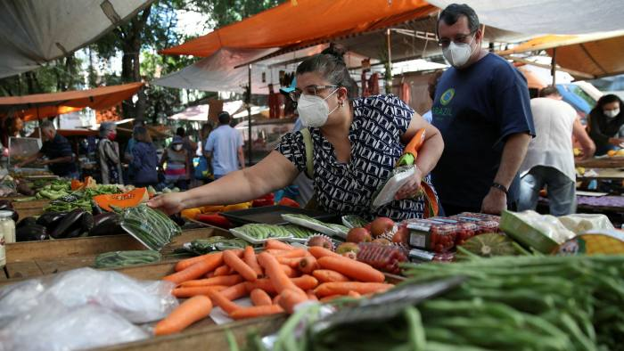 A woman picks up a melon at at street market