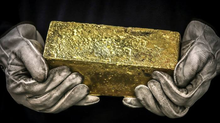 A Twenty kilogram gold brick is handled by a worker at the ABC Refinery smelter in Sydney