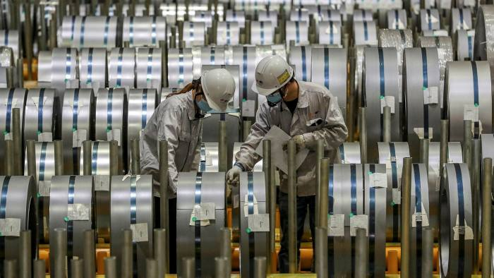 Workers check rolls of sheet aluminium at a factory in Wuhan, China