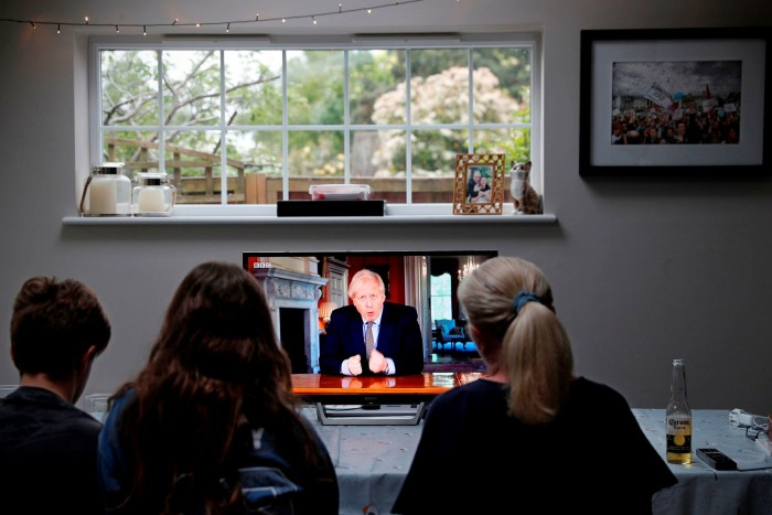 A family gathers round a TV to watch UK prime minister Boris Johnson's televised message on coronavirus on May 10